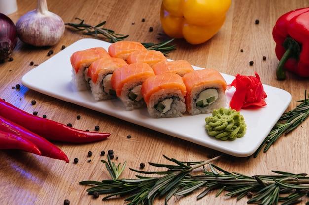 Appetitoso rotolo di sushi philadelphia con cetriolo formaggio e salmone su sfondo nero