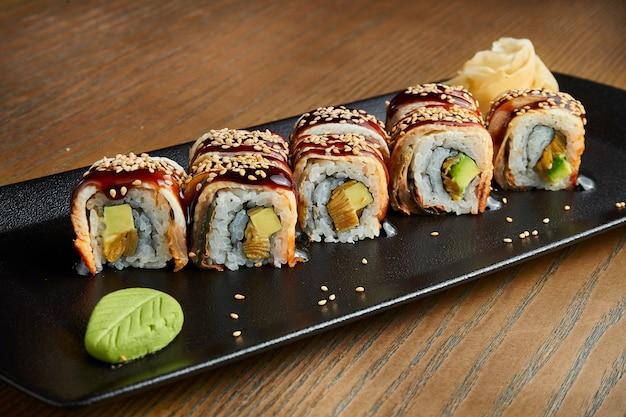 Involtini di sushi appetitosi - drago d'oro. rotoli con anguilla, salsa teriyaki e avocado su un piatto nero su una superficie di legno. effetto pellicola durante la posta. focalizzazione morbida