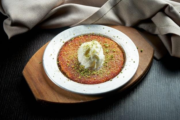 Appetitosa dolcezza turca kanafeh fatto con pasta fillo sminuzzata con miele, pistacchi e gelato bianco