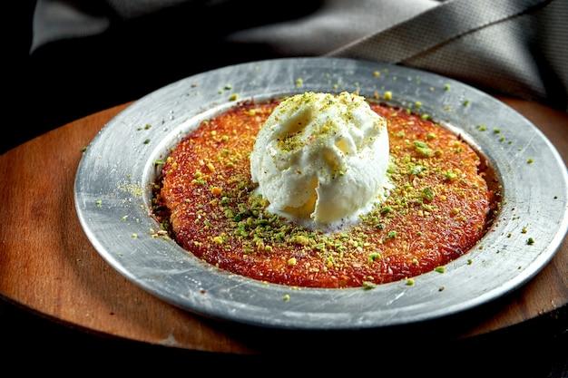 Appetitosa dolcezza turca kanafeh fatta con pasta fillo sminuzzata con miele, pistacchi e gelato bianco