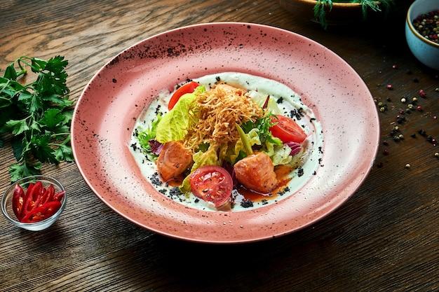 Appetitosa insalata calda con salmone al forno, pomodorini, citronella e salsa bianca, servita in un piatto bianco su un tavolo di legno. cibo del ristorante