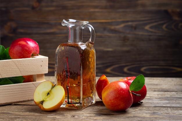 Aceto di sidro di mele e mela rossa fresca su uno sfondo di legno