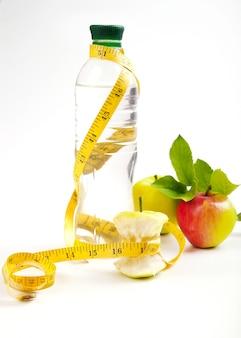 Nucleo di mela, acqua in bottiglia per una vita sana su uno spazio bianco