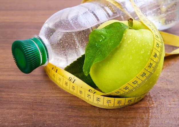 Nucleo di mela, acqua in bottiglia per una vita sana su uno spazio di legno