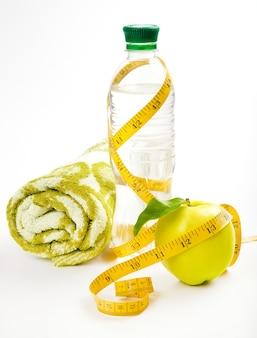 Nucleo di mela, asciugamano, acqua in bottiglia per una vita sana su uno spazio bianco