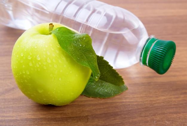 Nucleo di mela con gocce d'acqua, acqua in bottiglia per una vita sana