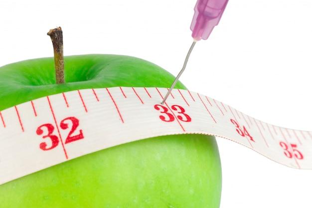 Ago di misurazione del nastro di misurazione verde mela isolato sulla parete bianca