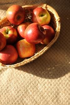 Raccolta di mele in un cesto con molti frutti rossi maturi sullo sfondo del copriletto con spazio per le copie
