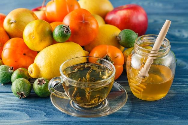Mela e miele sulla tavola di legno sopra la tavola blu