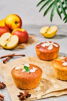 Muffin alle mele, con cannella e mele, scaglie di mandorle decorate con foglie di menta, primo piano, messa a fuoco selettiva, cornice verticale. tea time o colazione, torte fatte in casa