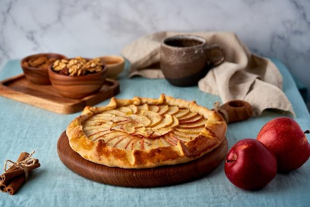 Torta di mele, galette con frutta, pasticceria dolce sul tavolo con tovaglia blu, crostata dolce