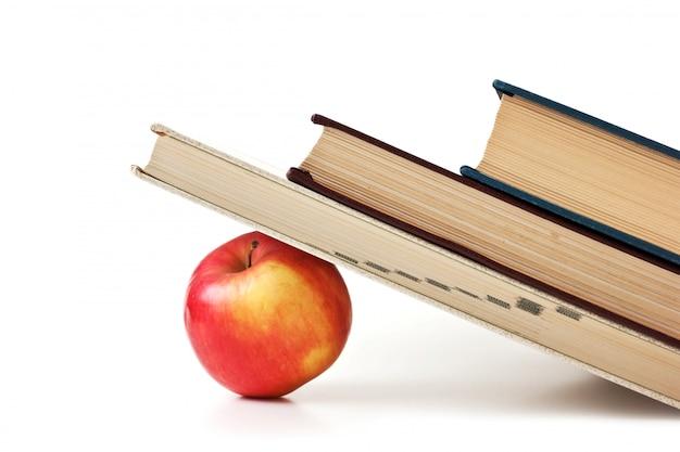 Mela sotto una pila di libri isolata on white