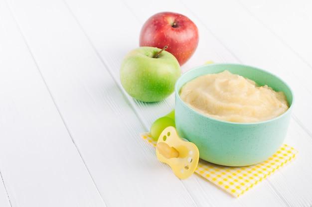 Purea di mele in una ciotola su legno bianco Foto Premium