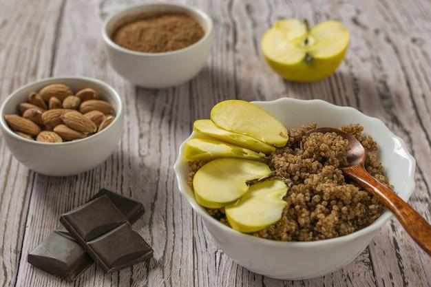 Fette di mela in una ciotola di quinoa e porridge di cioccolato su un tavolo di legno. dieta sana.