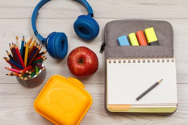 Apple, supporto per matite, lunch box, cuffie, quaderno su borsa-astuccio con pennarelli.