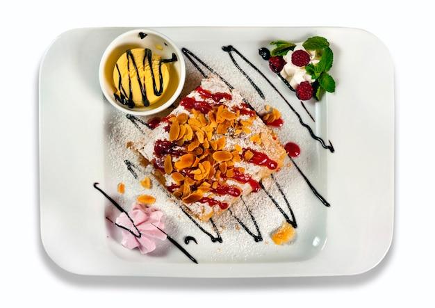 Strudel di mele con gelato su piatto bianco, isolato su sfondo bianco