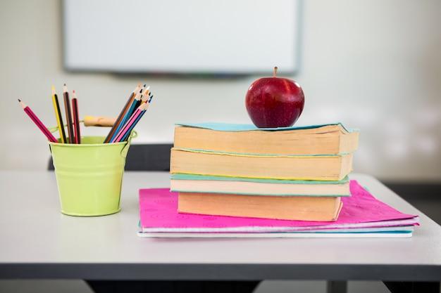 Apple con i libri e l'organizzatore dello scrittorio sulla tavola in aula