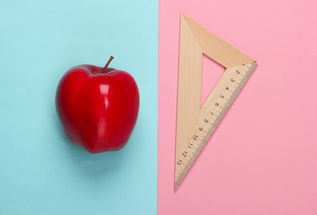 Apple, triangolo righello in legno su rosa blu. di nuovo a scuola. concetto di educazione