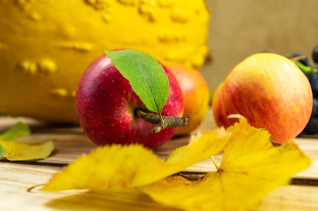 Mele in foglie d'autunno sullo spazio di legno giorno del ringraziamento