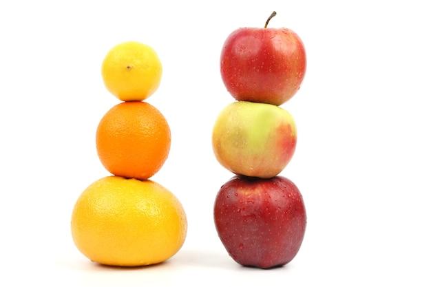 Le mele e gli agrumi stanno verticalmente l'uno sull'altro su sfondo bianco
