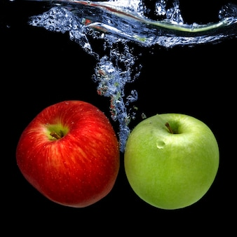 Le mele sono cadute in acqua con spruzzata isolata sul nero