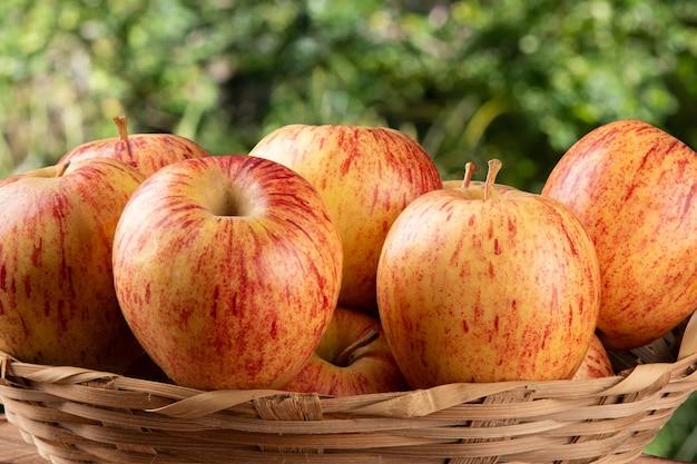 Mele frutti nel cesto con superficie sfocata.