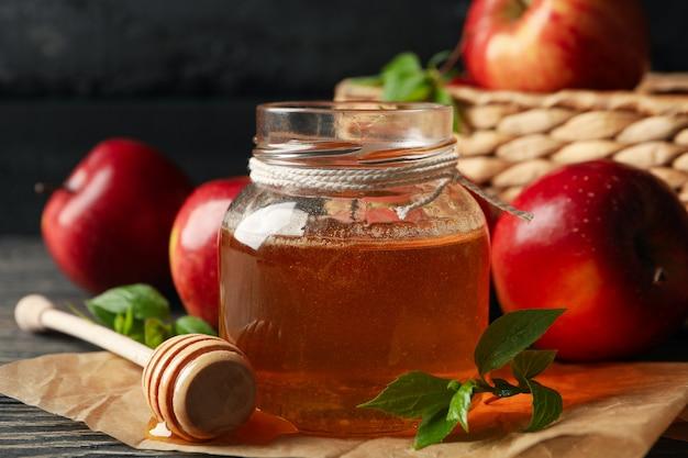 Mele e miele sulla tavola di legno, fine su