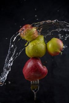 Mele e pere sulla forcella e spruzzi d'acqua.