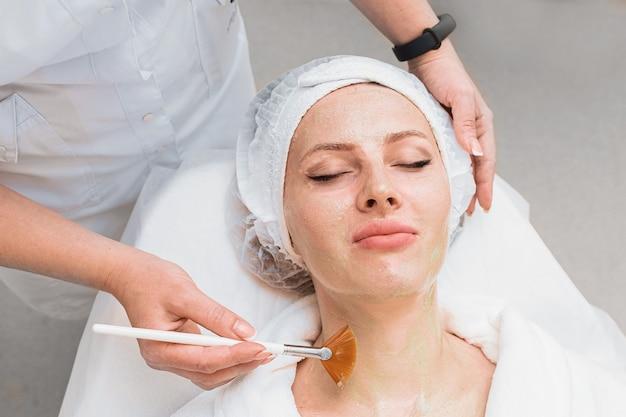 Applicazione di una maschera enzimatica con un pennello sulla vista dall'alto del viso di una donna.