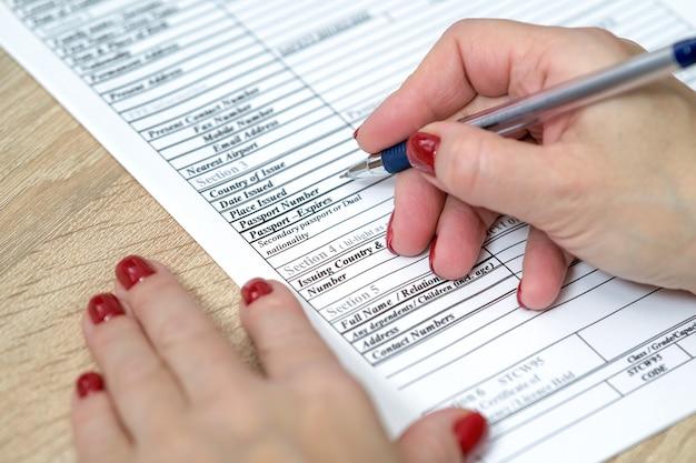 Modulo di domanda mano che tiene la penna pronta per compilare un elenco di domande modulo di domanda