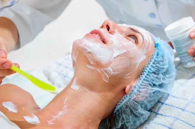 Applicazione di maschere dorate sul viso della modella. procedure cosmetiche