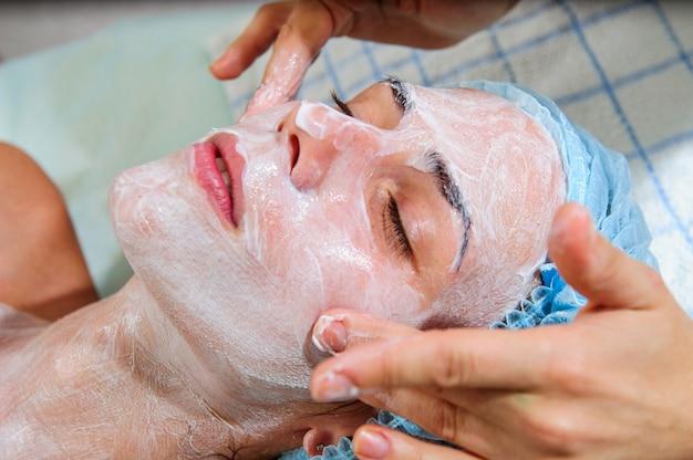 Maschere di applicazione sul viso del modello. procedure cosmetiche.