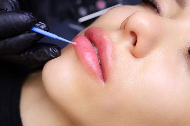 Applicare l'anestesia alle labbra della modella con un piccolo pennello blu prima della procedura di trucco permanente