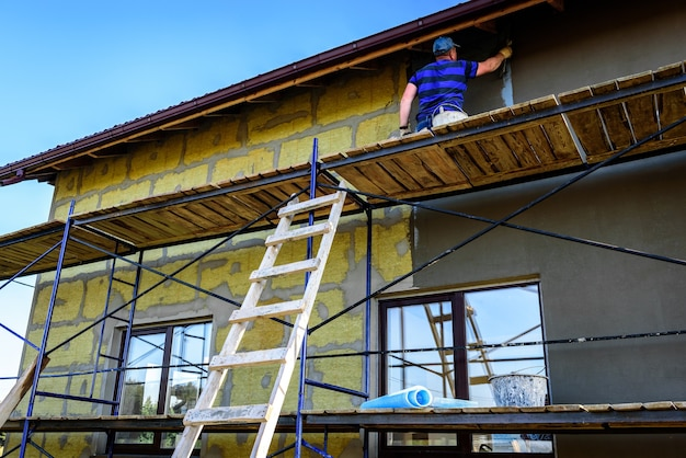 Applicazione di uno strato di colla da costruzione su parete isolata per la copertura di rete di rinforzo in fibra di vetro su lana minerale.