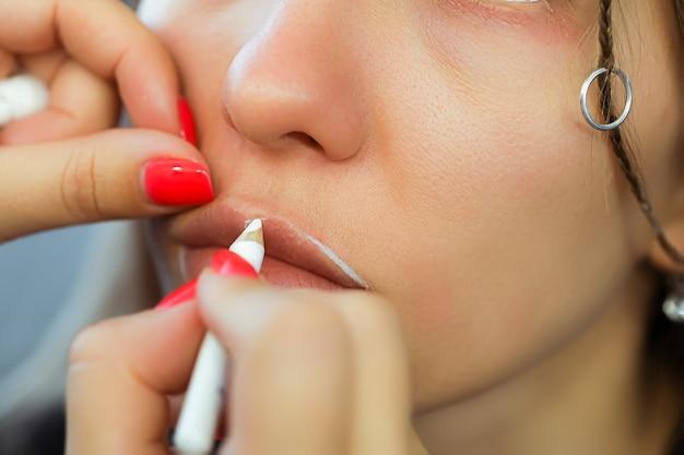 Applicare il contorno sulle labbra con una matita bianca prima della procedura di trucco permanente labbra