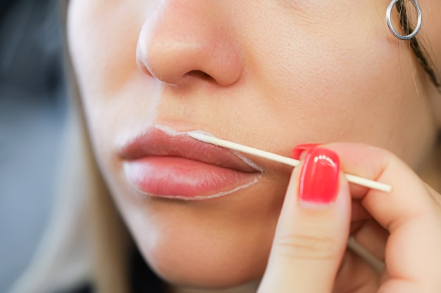 Applicare il contorno sulle labbra con una matita bianca prima della procedura di trucco permanente delle labbra