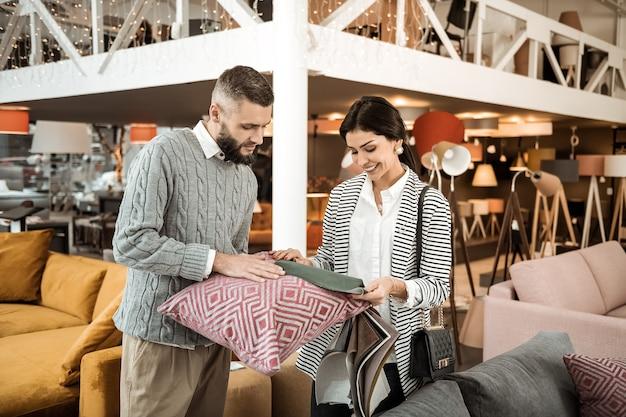 Applicazione di campioni. donna sorridente che trasporta pezzo di tessuto grigio mentre suo marito tiene il cuscino del divano