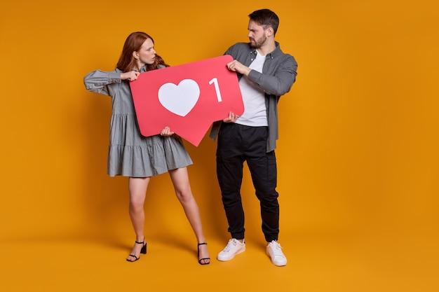 Apprezza il contenuto con il pulsante a forma di cuore. coppia che discute tenendo come icona dei social media, segno emoji da seguire iscriversi