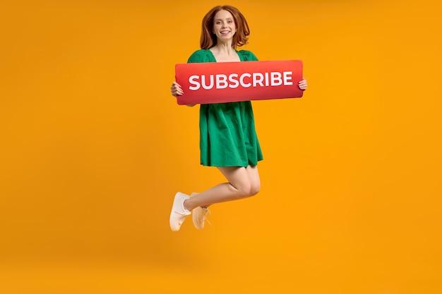 Apprezza i contenuti con il pulsante iscriviti femmina rossa che tiene come icona del segno dei social media per seguire...