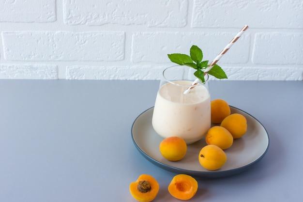 Frullato di albicocche o yogurt e albicocche mature su un tavolo. deliziosa bevanda a base di latte con albicocche mature.