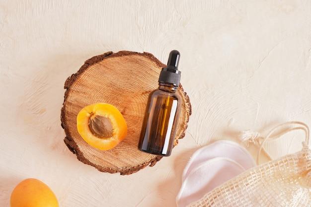 Albicocche e una bottiglia di vetro marrone con contagocce per cosmetici su fondo beige, olio o siero per la cura del corpo