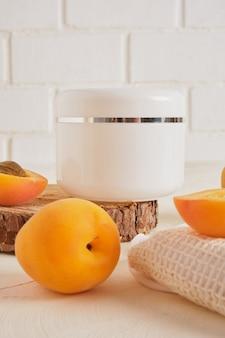 Barattolo di plastica bianca di albicocche per crema o cosmetici su un podio di legno da una sega tagliata da un albero su uno sfondo chiaro, contro un muro di mattoni bianchi