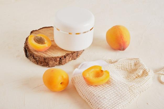 Barattolo di plastica bianca di albicocche per crema o cosmetici su un podio di legno da un legno tagliato a sega su uno sfondo chiaro
