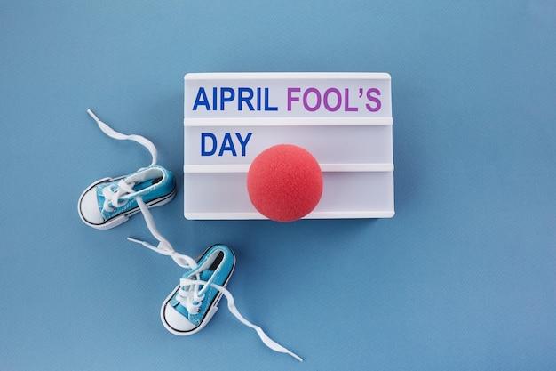 Primo d'aprile. simbolo di sorpresa. lacci delle scarpe legati insieme su fondo di legno blu. pesce d'aprile.