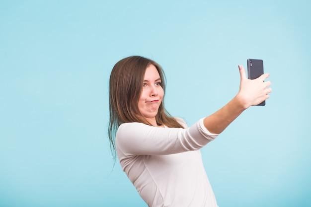 Concetto di giorno degli sciocchi di aprile - la donna pazza sciocca fa selfie. felice espressione