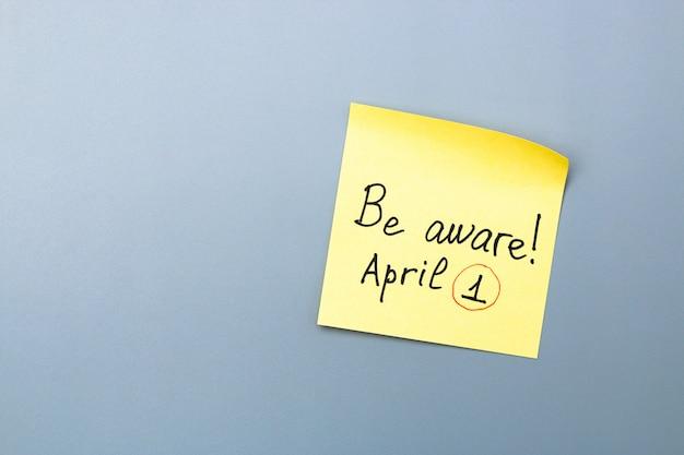 Promemoria del giorno dei pesci d'aprile sulla nota appiccicosa gialla. fai attenzione e non lasciarti ingannare