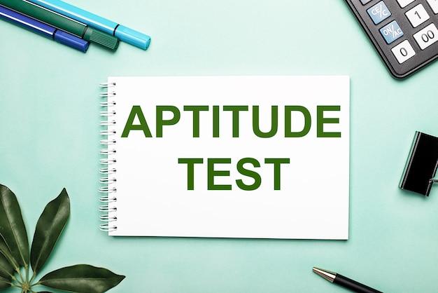 Aptitude test è scritto su un foglio bianco su sfondo blu vicino alla cancelleria e al foglio scheffler.