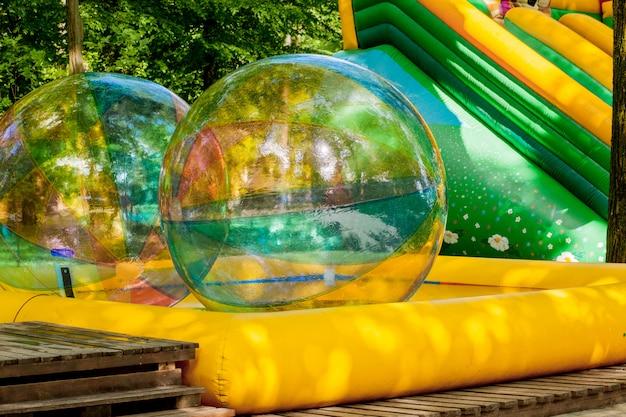 Aqua zorbing. palline da passeggio colorate. attività acquatiche per bambini. bambini che giocano insieme e si divertono all'interno di una grande sfera gonfiabile in una piscina