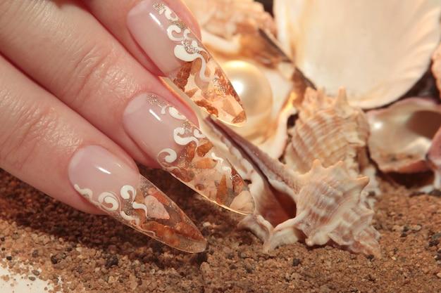Nail art nautica per acquari su unghie lunghe trasparenti con piccole conchiglie all'interno e paillettes all'esterno