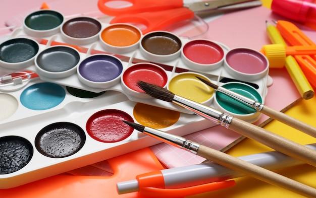 Vernici e pennelli aquevrelic su sfondo giallo. materiale scolastico, accessori per artisti